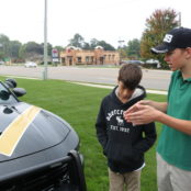 Joshua and Jessie admire the 100 year special paint job on the Dodge Charger